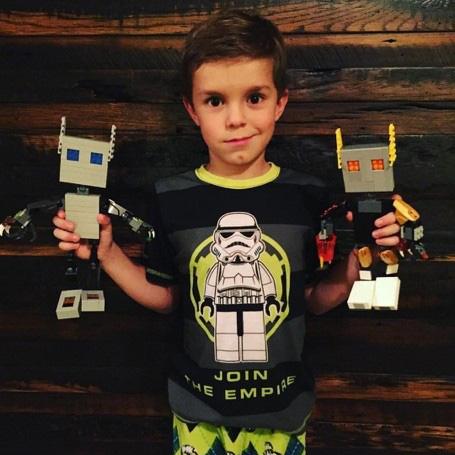 Boy holding robots he built