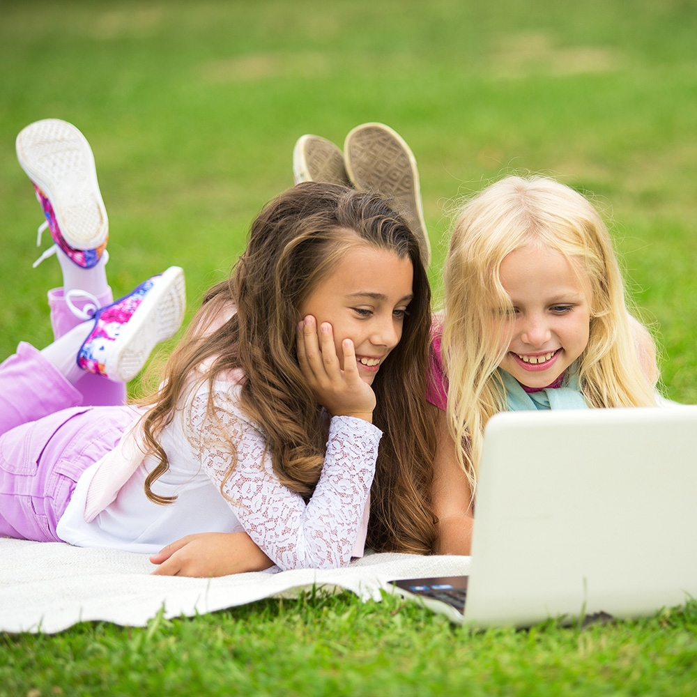 Girls outside on their laptop for Virtual camp