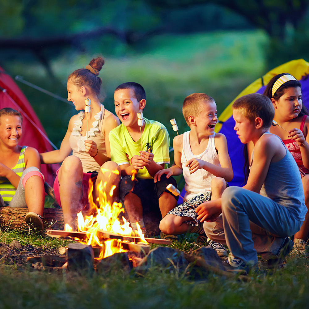 Kids around a campfire for sleep away camp